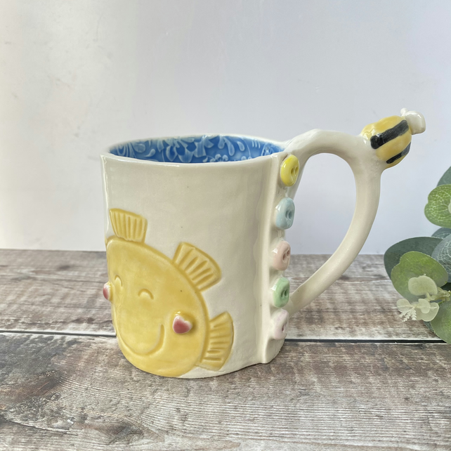 Handmade porcelain mug, sunshine and bee with button detail.