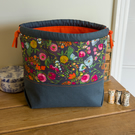 Drawstring project bag made with bright floral print in grey and orange