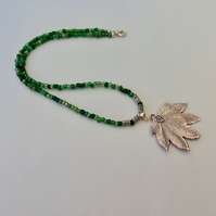 Green seed bead necklace with a Tibetan silver leaf pendant.