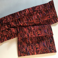 Red patterned pleated face covering and pouch