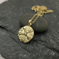 Gold flower pendant with a diamond centre on a gold chain