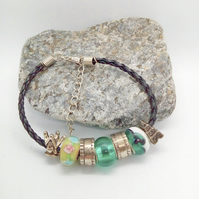 Green Lamp-work Bead Bracelet with Silver Charms on a Plaited Leather Band