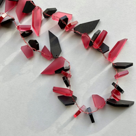 Contemporary long raspberry pink and black acrylic necklace.