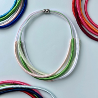 Contemporary multi-strand pastel cord and mesh five strand necklace.