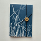 Notebook. Pocket sized. Swallow over grassland.