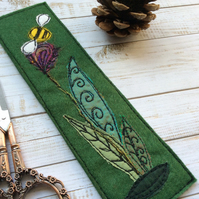 Embroidered bee and flower bookmark.
