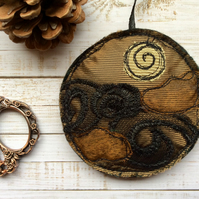 Upcycled embroidered gold decoration.