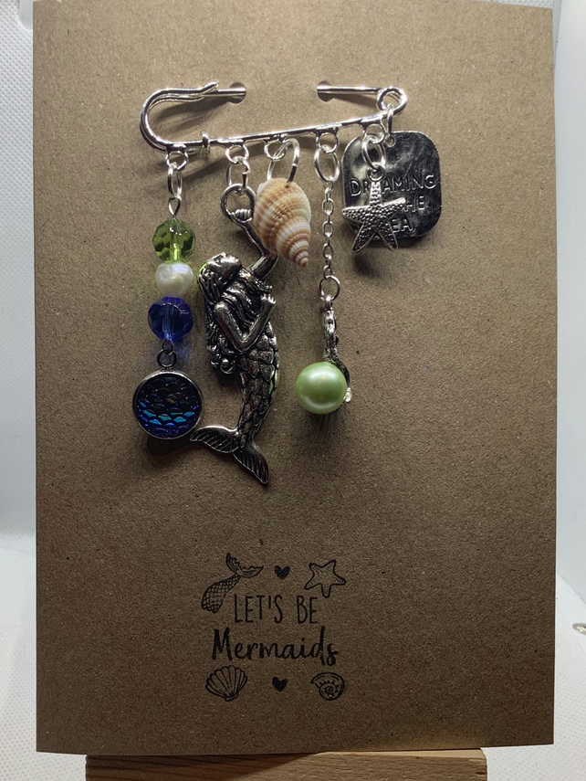 Handmade kilt pin mermaid themed brooch, attached to kraft greetings card.