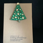 A handmade, felt,  Christmas Tree brooch, attached to a hand stamped kraft card