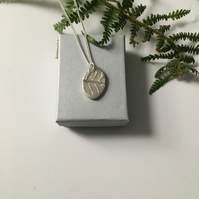 Oval pendant imprinted with a Fern leaf