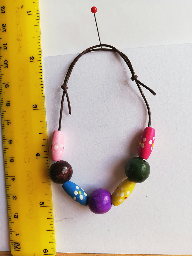 multicoloured wooden beads on leather bracelet