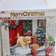 Christmas card showing puppy at the door with presents on the step