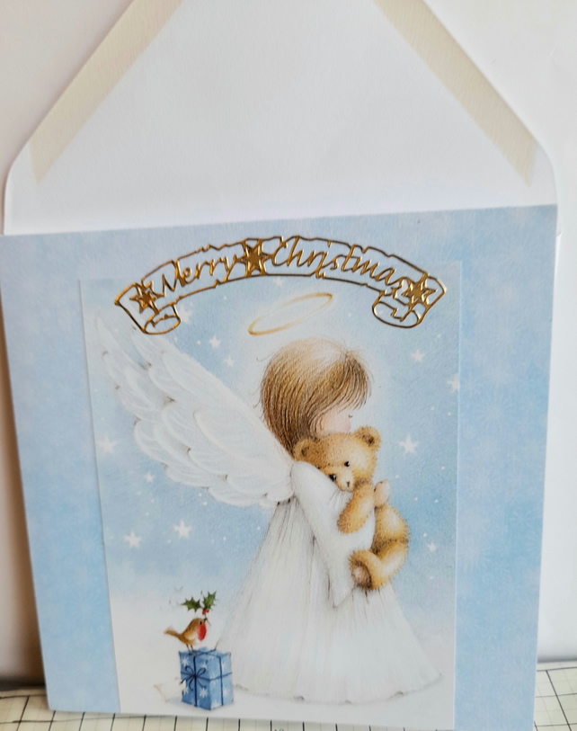 Christmas card showing angel with teddy bear on blue snowflake background