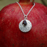 Winter's Return Eco Silver textured disc pendant with garnet pomegranate seed