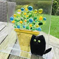Fused glass cat and flower pot ornament .