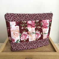 Toiletry bag in damson & white floral panelled design.