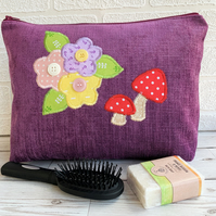 Purple toiletry bag with red mushrooms and pastel flowers