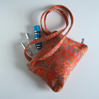 Handbag or shoulder bag in a tapestry effect fabric with chunky zip closure.