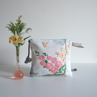 Make up or cosmetics bag sewn from floral embroidered vintage table linen.