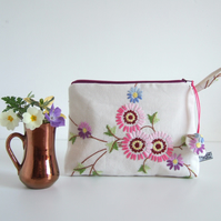 Make up or cosmetics bag made from floral embroidered  vintage table linen.