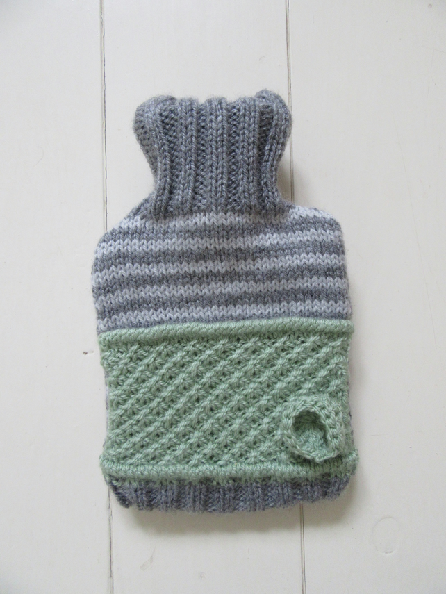 Knitted grey stripy hot water bottle cover with daisy stitch detail