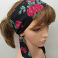 Women tie back black floral head scarf.
