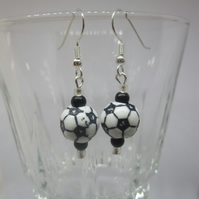A Pair of Black and White Themed Earrings.