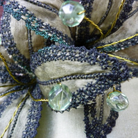 Green silk fascinator with individually embroidered flowers.