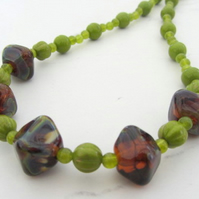 Dark amber lampwork glass necklace with green melon beads