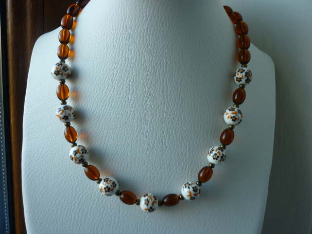 BROWN, WHITE AND BRONZE CERAMIC BEAD NECKLACE.  1077