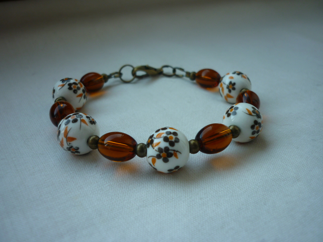 BROWN, WHITE AND BRONZE CERAMIC BEAD BRACELET.  1078