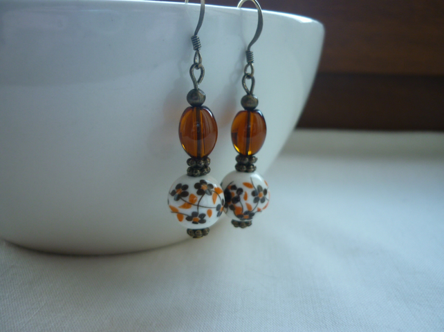 BROWN, WHITE AND BRONZE CERAMIC DANGLE EARRINGS.  1079