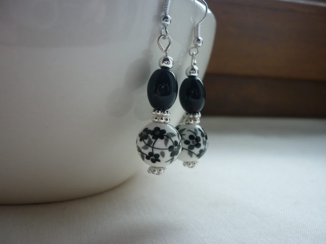 BLACK AND WHITE PORCELAIN FLORAL BEAD EARRINGS.  840