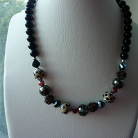 BLACK, BRONZE, BEIGE, BROWN AND SILVER NECKLACE.