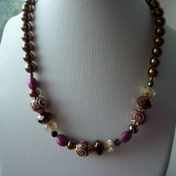 PINK, BRONZE, IVORY AND GOLD NECKLACE.