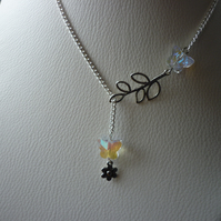 AB CRYSTAL AND SILVER, BUTTERFLY, LEAF AND FLOWER LARIAT NECKLACE.