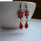 RED, CRYSTAL AND BRONZE FLOWER DANGLE EARRINGS.