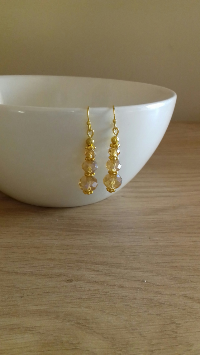 FACETED GOLD RONDELLE GLASS BEAD EARRINGS.