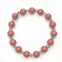 Stretchy bracelet with red glass pearls and silver plated spacers.