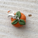 two handmade pumpkin stitch markers