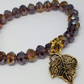 Bronze coloured glass bead stretch bracelet with charm