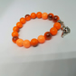 Bright Cheerful Orange Glass Bead Stretchy Bracelet with fish charm.