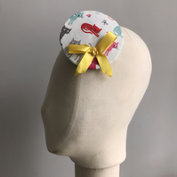 Rainbow coloured cat print fascinator with a yellow bow