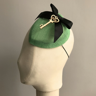 Green Percher Cocktail Hat, with a Black Bow and Key.