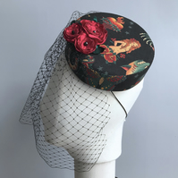 Tattoo print pillbox hat with a birdcage veil and red roses