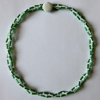 A crocheted necklace in white cotton with green bugle beads