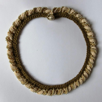 A crocheted necklace in coffee and cream cotton with edging of gold beads