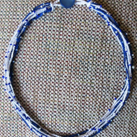 A crocheted necklace in blue and white crochet cotton with tiny beads
