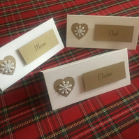 Personalised Christmas Place Card With A White Pearl Snowflake On A Gold Heart