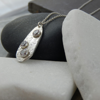 Irregular shaped textured Silver pendant set with Cubic Zirconia gemstones